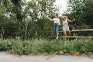 Two happy young women jumping from fence in a park - KNSF03078