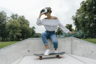 Young woman with skateboard wearing VR glasses in a skatepark - KNSF03081
