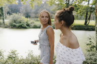Two young women with cell phone walking at the waterfront - KNSF03099
