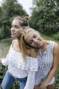Smiling young woman resting on female friend's shoulder - KNSF03102