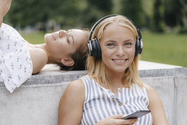 Portrait of young woman with cell phone and headphones in a skatepark - KNSF03111