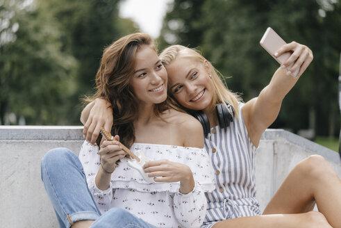 Two happy young women taking a selfie in a skatepark - KNSF03117