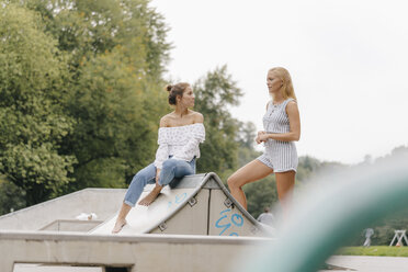 Two young women talking in a skatepark - KNSF03129