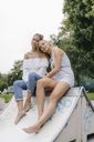 Young woman sitting in skatepark resting on female friend's shoulder - KNSF03135