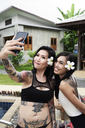 Two happy women taking a selfies at swimming pool - IGGF00237