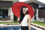 Portrait of smiling woman with flower in her hair holding a red tradtional umbrella at a swimming pool - IGGF00240