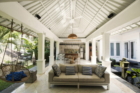 Open living area in a tropical luxury home with couch and hanging chair - SBOF00921
