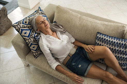Attractive senior woman relaxing on couch - SBOF00933