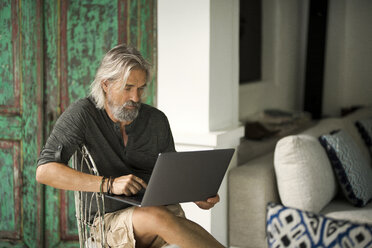 Senior man working on laptop in his stylish home - SBOF00948