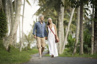 Handsome senior couple strolling through tropical landscape with palm trees - SBOF00960