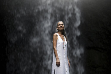 Beautiful senior woman standing in front of a tropical waterfall - SBOF00966