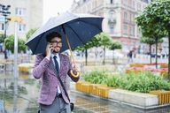 Fashionable businessman on the phone on rainy day in the city - BSZF00099