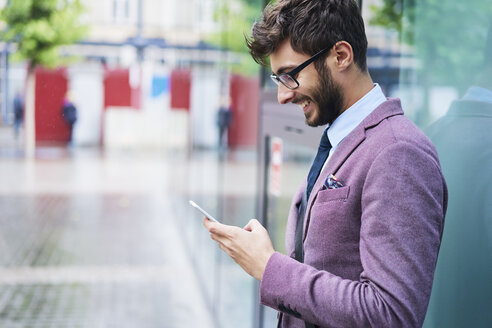 Fashionable businessman checking his cell phone - BSZF00102