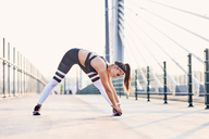 Young athletic woman stretching after urban workout - BSZF00110