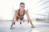 Fit woman doing pushups outdoors - BSZF00119
