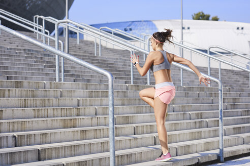 Fit young woman running on stairs - BSZF00122