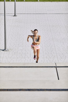 Fit young woman running on stairs - BSZF00125