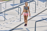 Fit young woman skipping rop outdoors - BSZF00134