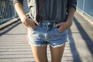Young woman wearing jeans shorts, partial view - KNSF03144