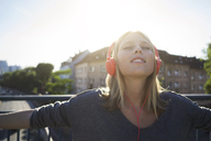 Portrait of young woman with eyes closed listening music with headphones - KNSF03147