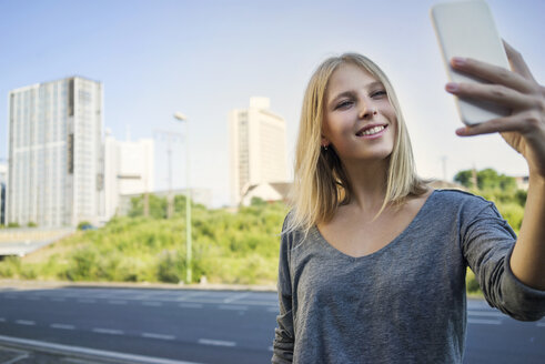 Portrait of smiling young woman taking selfie with smartphone - KNSF03153