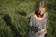 Young woman on a meadow using cell phone - KNSF03159