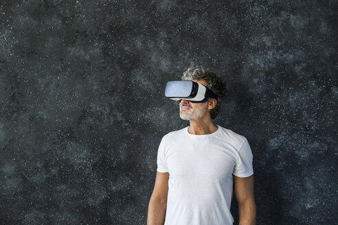 Mature man looking through VR glasses - HAPF02469