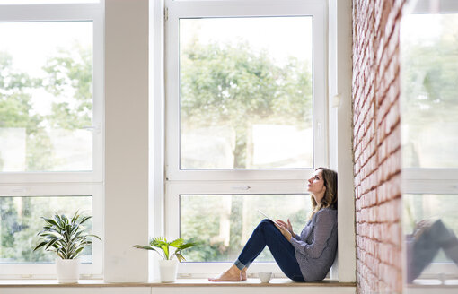 Woman sitting at home on the window sill, reading a book - HAPF02487