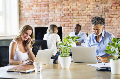 Business people working in office, using smartphone and laptop - HAPF02493