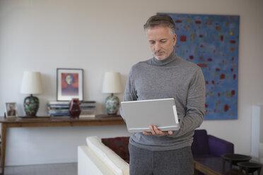 Businessman using laptop in apartment - SUF00378