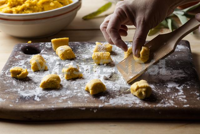 Preparing pumpkin gnocchi, rolling on wooden board - SBDF03394