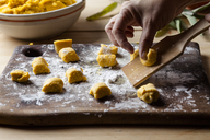 Preparing pumpkin gnocchi, rolling on wooden board - SBDF03394