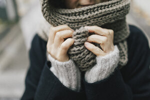 Woman's hand holding knitted scarf, close-up - KMKF00089
