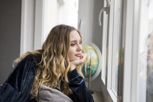 Portrait of daydreaming young woman looking through window - FMKF04646