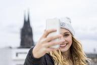 Germany, Cologne, portrait of laughing young woman taking selfie with smartphone - FMKF04661
