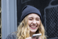 Portrait of laughing young woman with smartphone - FMKF04664