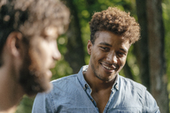 Young man smiling at friend - KNSF03168