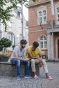 Two friends sharing cell phone in the city - KNSF03171