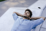 Portrait of relaxed man lying in skatepark - KNSF03186