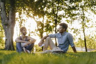 Two friends sitting in a park with mobile device and papers - KNSF03198