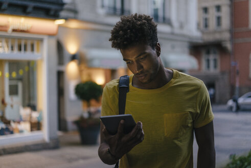 Man looking at phablet in the city at dusk - KNSF03204