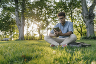 Young man sitting in park using mobile device - KNSF03228