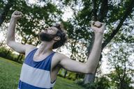 Man raising his arms in a park - KNSF03231