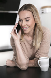 Portrait of blond woman on the phone at home - GDF01173