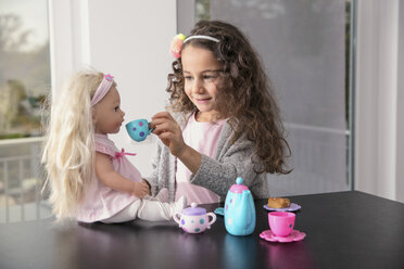 Portrait of smiling little girl playing with doll and doll's china set - GDF01179