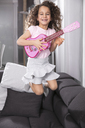 Portrait of happy little girl with pink toy guitar jumping in the air on the couch - GDF01182