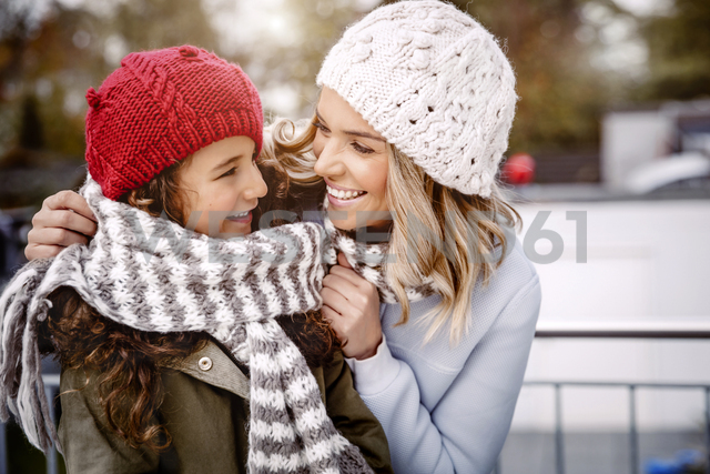 Happy mother and her little daughter wearing woolly hats and knitted scarf - GDF01185