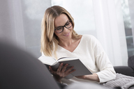 Smiling woman reading book on the couch - GDF01194