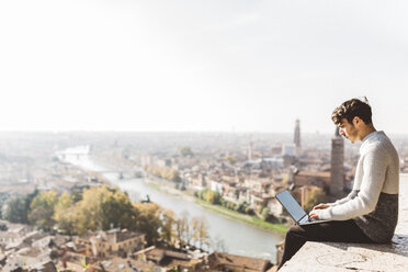 Italy, Verona, tourist using laptop, observation point - GIOF03580