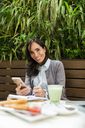 Portrait of smiling businesswoman working at an outdoor cafe - VABF01392